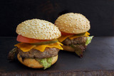 Tasty grilled delicious burger with lettuce, cheese, onion and tomato on a rustic wooden plank