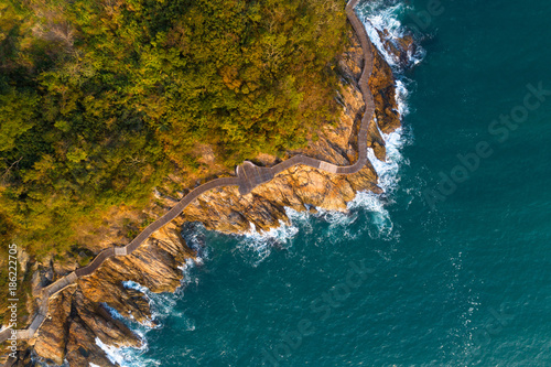 Fotobehang Groen blauw aerial drone view of wooden boardwalk and sea waves break on rocks at coast