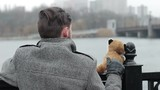 A lonely man standing on a bridge with a soft toy by the river. The concept of depression and loneliness in youth - 186245980