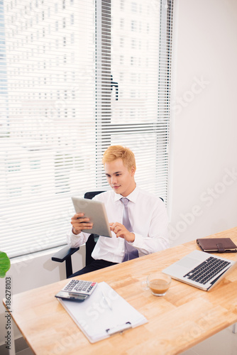Smiling young man using digital tablet in the office - 186278103