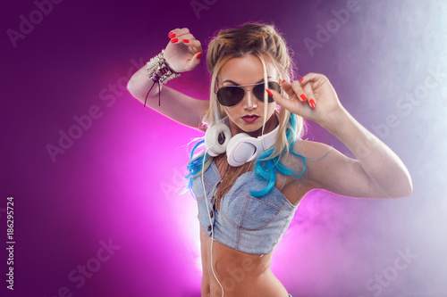Young fashionable girl in disco style. Listening music and enjoying. Retro style - 186295724
