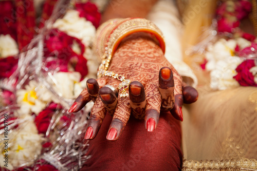 Foto Murales Beautiful female hand of an Indian bride, holding groom's hand during a typical Hindu wedding ceremony.