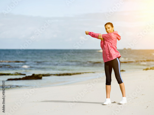 Young woman at the beach doing exercises - 186297507