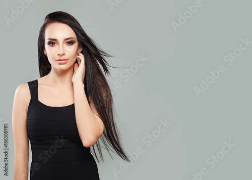 Foto op Canvas Kapsalon Young Perfect Woman with Long Blowing Hair and Natural Makeup on Gray Background with Copy space