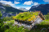 Typical norwegian old wooden houses with grass roofs near Sunnylvsfjorden fjord and famous Seven Sisters waterfalls, western Norway.