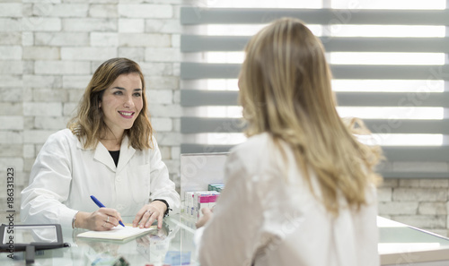 Poster Apotheek Woman customer in pharmacy with doctor woman ready for prescription