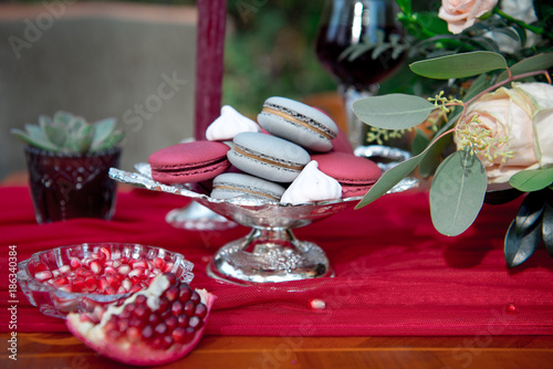 Fotobehang Macarons Silver serving dish with pomegranate and macarons