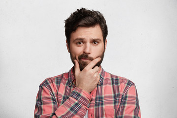 Portrait of confused bearded male has trendy hairdo, curves lips and keeps hand on chin, looks with hesitant expression, dressed in fashionable checkered shirt, isolated over white background