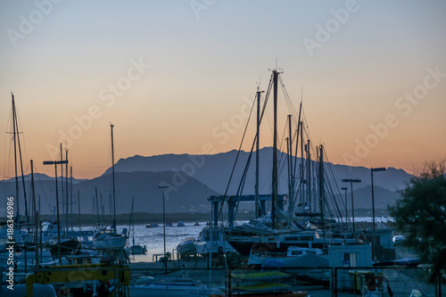 In de dag Rio de Janeiro Sunset view of a marina dock with sailing and motor boats and a mountainous landscape in the background