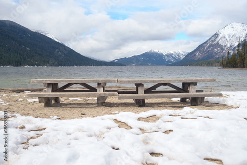 Fotobehang Wit Picnic tables on winter beach of mountain lake