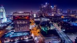 Cinematic urban aerial view of downtown streets with city skyline at night