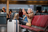 Full length portrait of old lady is sitting on bench at airport lounge. She is having video call using smartphone and earphones while putting legs on suitcase and looking at screen of gadget - 186395347