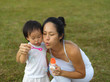 asian chinese female parent blowing bubbles with baby girl