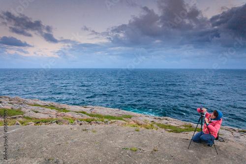 Tourist with camera on seashore, Norway