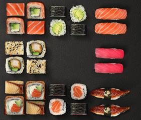 Japanese cuisine. Sushi and rolls set over dark background.
