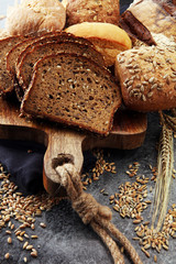 Sliced rye bread on cutting board. Whole grain rye bread and rolls with seeds.