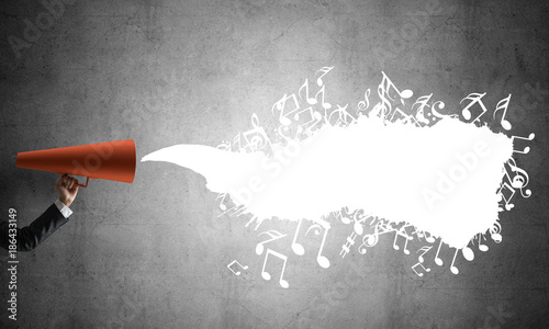 Hand of businesswoman holding red paper trumpet against concrete background