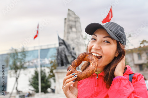 Happy woman eating traditional turkish bread bagel in Istanbul, Turkey