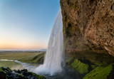 Sunset at the back of Seljalandsfoss waterfall in Iceland