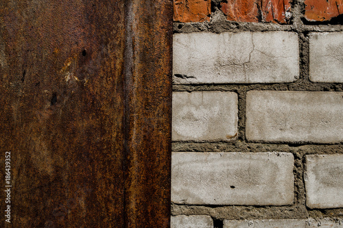 Metal door and old brick wall. Old brick wall texture background. Rusty metal door - 186439352