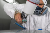 Painter spray gun in the hands of a painter. - 186447112