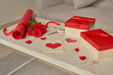 Love gift wrapping with rolls of  paper and bouquet of roses