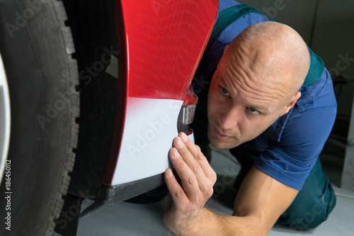 Man checks the softness of the paint on the car.