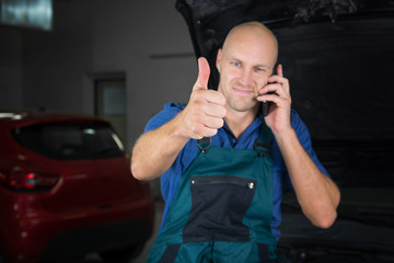 Young mechanic showing a raised thumb in a car shop while he calls.