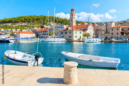 Fishing boats in Pucisca port with beautiful church in background, Brac island, Croatia