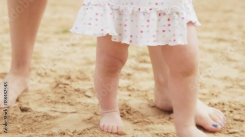 First baby's steps on the sandy beach, slow motion