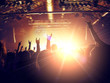 Concert venue crowded with ecstatic fans clapping in front of a stage