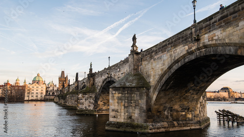 Foto op Aluminium Praag Sunny winter late afternoon in Prague. Charles bridge and town shot from beneath. Under the bridge span in distance seen National theater. Softly illuminated by low winter sun.
