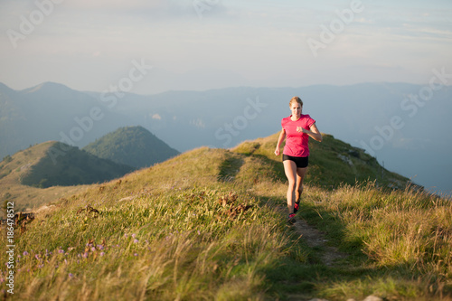 In de dag Jogging Woman runs on a top of the mountains with mountain range in background