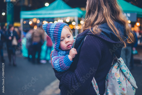 Young mother carrying baby in city