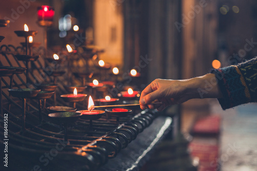 Hand of young woman lighting votice candles - 186495582