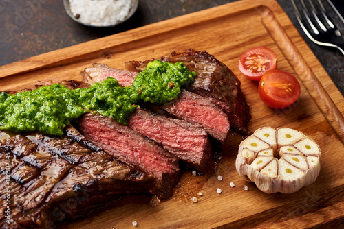 Fotobehang Steakhouse Grilled Black Angus Steak with tomatoes, garlic with chimichurri sauce on meat cutting board.