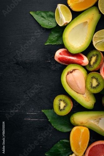 Fruit on a wooden background. Avocado, lime, orange, grapefruit and kiwi. Top view. Free space for your text.