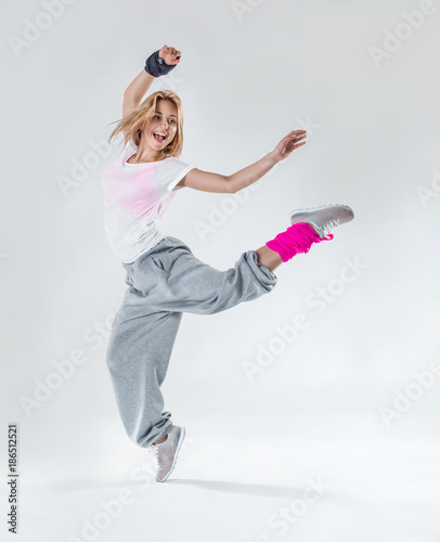 Fototapeta Young beautiful slim girl dancing on a white studio background
