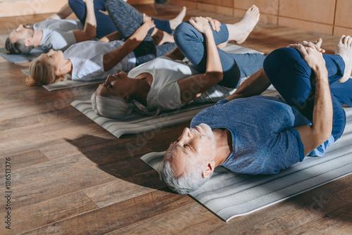 Leinwanddruck Bild group of senior people stretching in yoga mats in studio