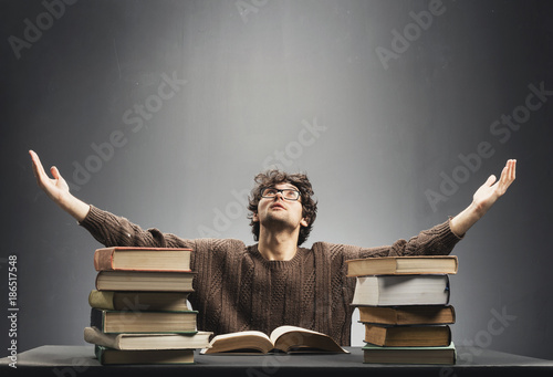 Foto Murales Helpless young man sitting at the desk full of books.