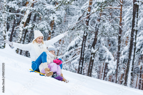 happy daughter and mother sledging together in winter park - 186520320