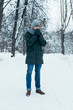 young man warming hands up while walking in snowy park