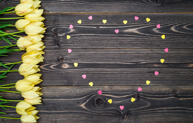 Spring background with heart from colored sprinkles and yellow tulips border on wood background, copy space. Flat lay, top view. Holiday greeting card for Valentines Day, Womans Day, Mothers Day