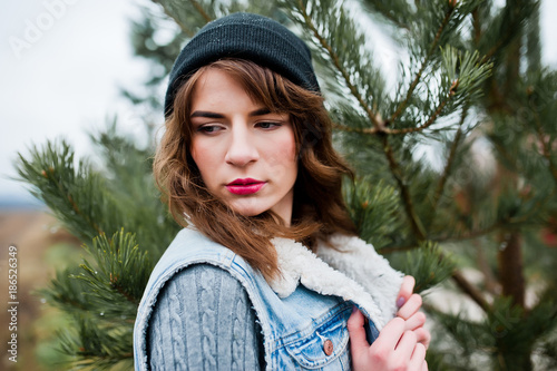 Portrait of brunette girl in hat and jeans jacket at christmas tree.
