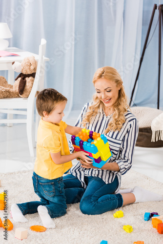 mother and little son playing with toys together on floor at home