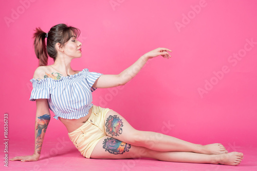 Girl, woman with tattoo on pink background, Pin up style - 186536733