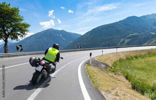 Foto op Plexiglas Motorsport Motorradfahrer fährt mit seinem Motorrad auf kurvigen Straßen durch die Berge und einer wunderschöne Landschaft