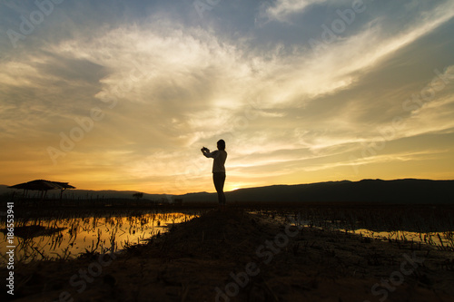 Staande foto Zwart Landscape nature scene of women shooting the photo at dramatic sky of beautiful sunset.