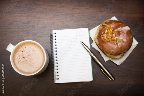 Open notebook, tasty donut and cup of coffee on brown wooden table, copy space. - 186556360