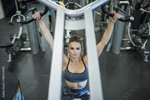 Mature woman training shoulders and back at gym machines © FotoAndalucia